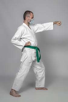 Практикующий дзюдо носит защитную маску во время тренировки. спорт во время коронавируса