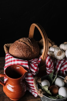 Jug and eggs near basket with food