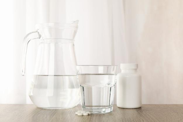 Кувшин и стакан воды и таблетки на деревянном столе, крупным планом