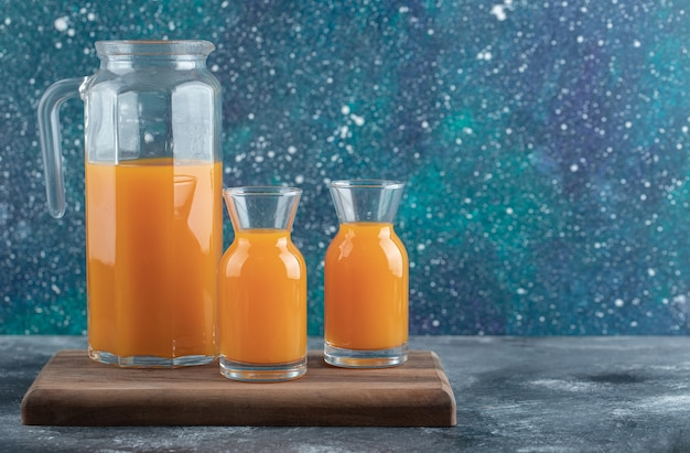 木の板に水差しとオレンジジュースのグラス。