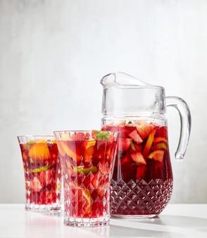 レストランのテーブルの上の赤いサングリアの水差しとグラス