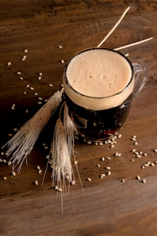 Jug of beer with spike barley on wooden table