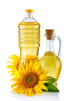 Jug and bottle of sunflower oil with flower isolated on white