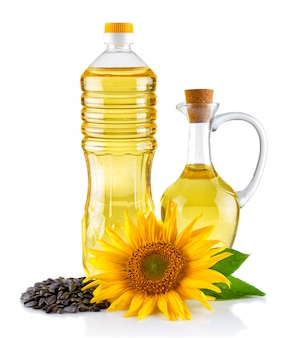 Jug and bottle of sunflower oil with flower and seeds isolated