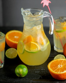 A jug of citrus beverage with orange and lime slices