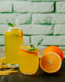 Brocca di agrumi limonata vetro arancione menta acqua frizzante vista laterale