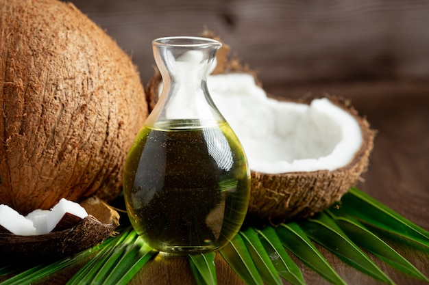 Jug of coconut oil whit coconut put on dark background Free Photo