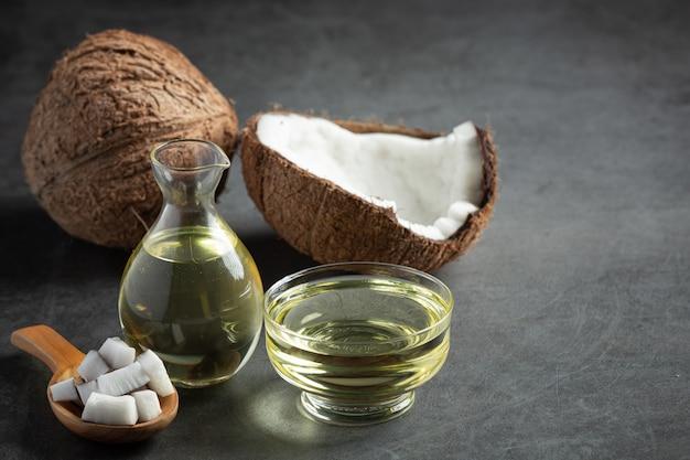 Brocca di cocco con olio di cocco messo su sfondo scuro