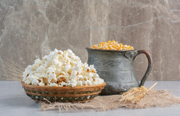 A jug of corn grains and a single wheat stalk next to a weaved basket of popcorn on a piece of cloth on marble surface