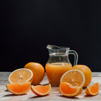 Jug of delicious orange juice surrounded by glasses and oranges front view