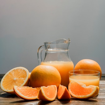 Jug of delicious orange juice surrounded by glasses and oranges
