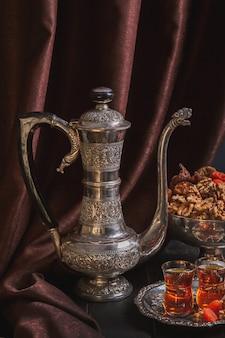 Кувшин для воды или чая, ваза с сухофруктами и тарелка с чаем в бокалах для армуды