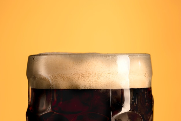 Jug of fresh beer with foam on orange background