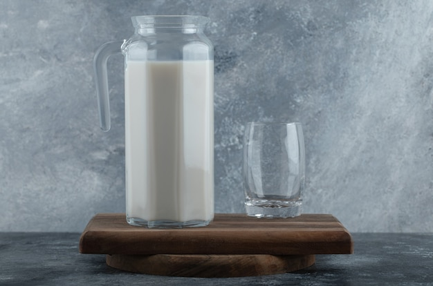 Jug of fresh milk and glass of water on wooden board.