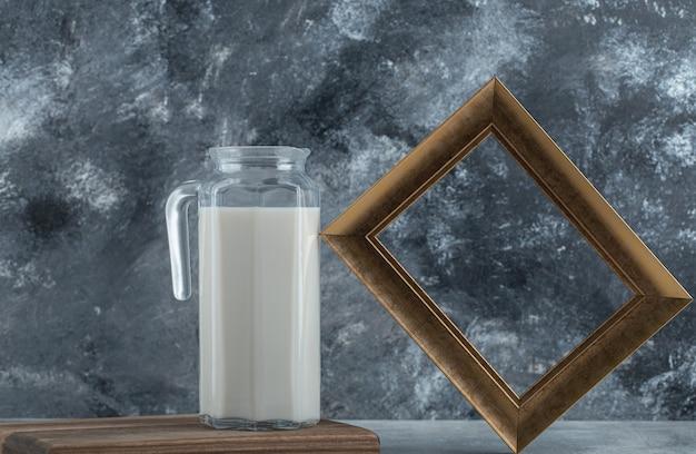 Brocca di latte fresco e cornice portafoto su marmo.