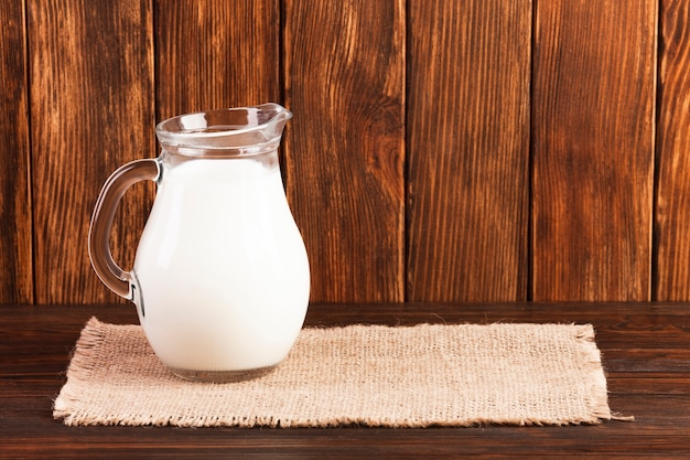 Jug of fresh milk on wooden table