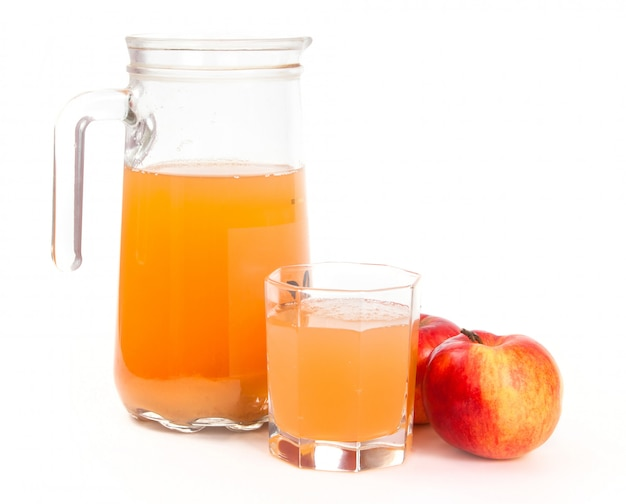 Jug of freshly squeezed apple juice, glass and two apples