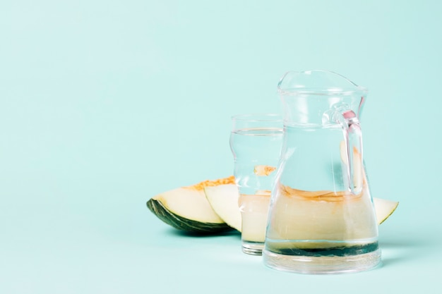 Jug and glass of water with slices of melon