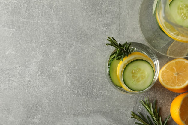 Jug and glass with cucumber water on grey table