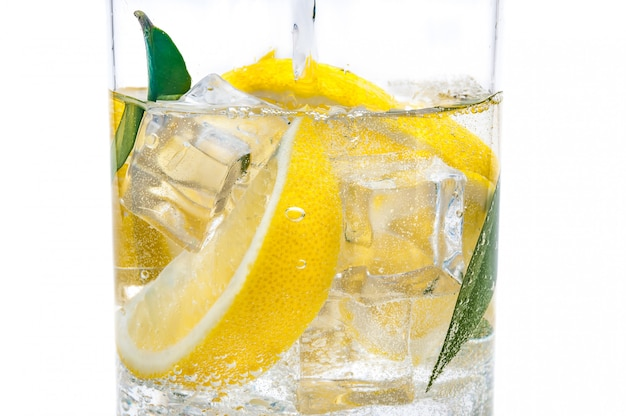 In the jug is a drink of ice, the lobules of a fresh juicy yellow lemon and crystal clear water.