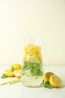 brocca di limonata, limoni e cannucce sulla tabella strutturata bianca