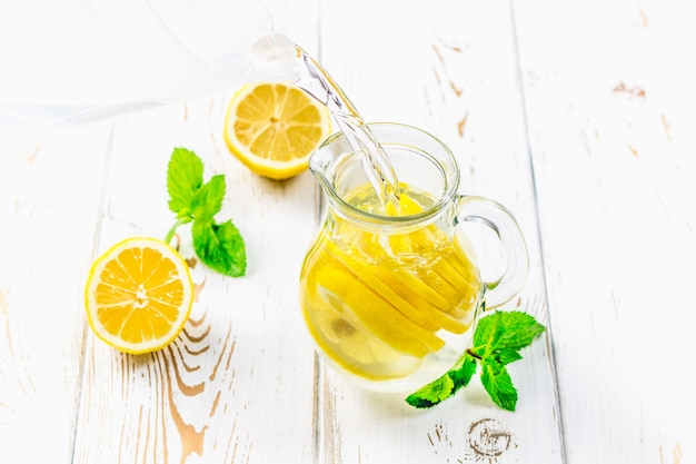 In a jug of lemons pour water on a white wooden background.