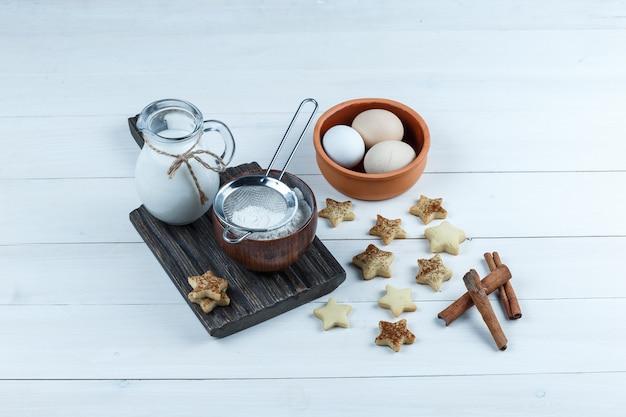 Brocca di latte, ciotola di farina, filtro per farina in una tavola di legno con biscotti a stella, cannella, uova close-up su una tavola di legno bianca sullo sfondo