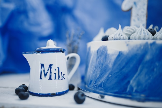 Jug of milk and cake on a blue background next to a vase with branches of lavender