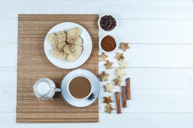 Brocca di latte, tazza di caffè, biscotti a forma di cuore su una tovaglietta con chicchi di caffè e farina, biscotti a stella, cannella vista dall'alto su un fondo di tavola di legno bianco