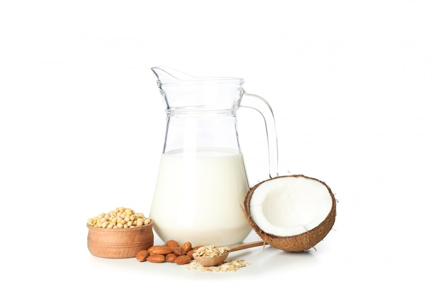 Jug of milk, soybeans, almond, oatmeal and coconut isolated on white