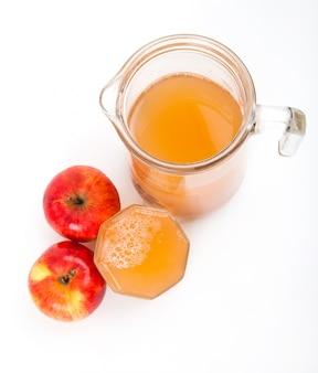分離された2つのリンゴとリンゴジュースの水差し