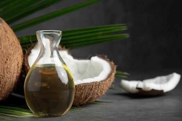 Кувшин кокосового масла и кокоса на темном фоне
