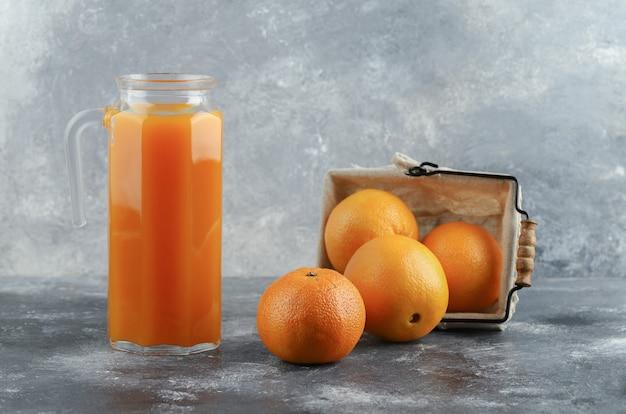 Кувшин сока и корзина апельсинов на мраморном столе.