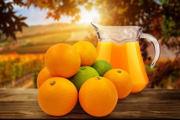 오렌지와 달콤한 레몬 주스 한 병과 그 안에 오렌지를 짜내는 사람