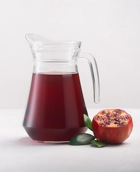 흰색 배경에 석류 과일 조각이 있는 석류 주스 한 병, 클로즈업