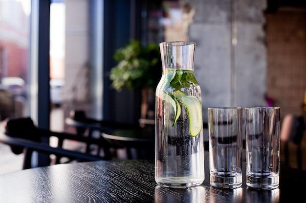 キュウリとミントとレストランのテーブルに2つの空のグラスと水差し