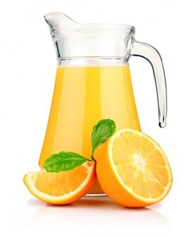 Jug of orange juice and orange fruits with green leaves