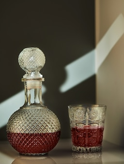 Jug of red wine and glass of wine, with unusual lighting in the form of patterns on the wall.