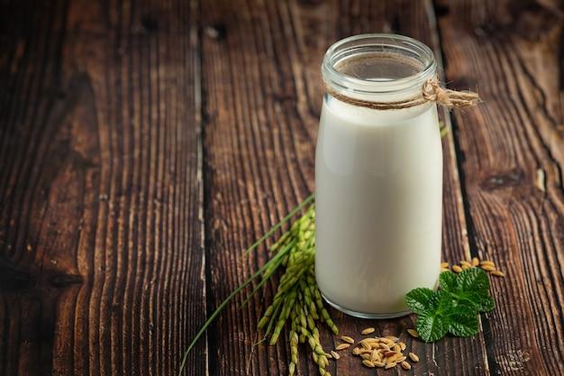 Brocca di latte di riso con pianta di riso e seme di riso messo sul pavimento di legno