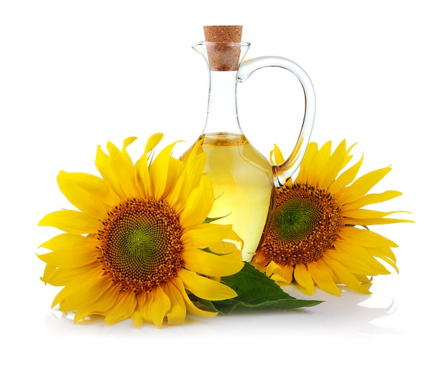 Jug of sunflower oil with flowers isolated