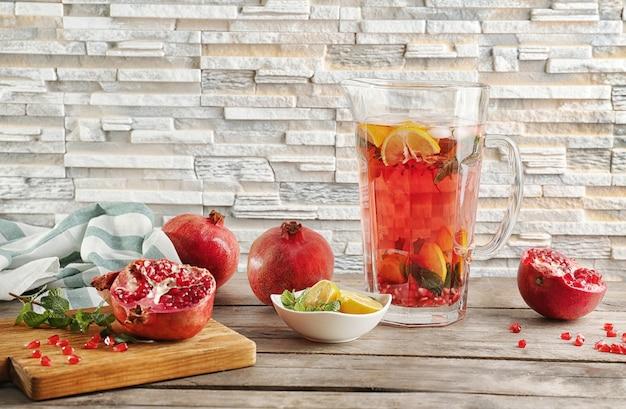 Кувшин с холодным фруктовым коктейлем на кирпичной стене стола
