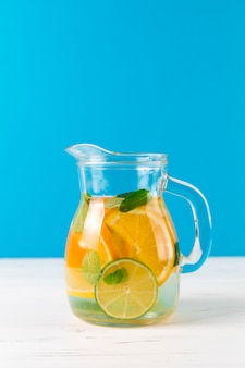 Jug with homemade lemonade with blue background