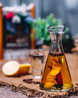 Кувшин с лимонным сорбетом и анисом с корицей и апельсиновой цедрой на виде сбоку