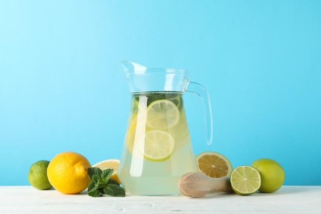 Кувшин с лимонадом против синей поверхности. свежий напиток