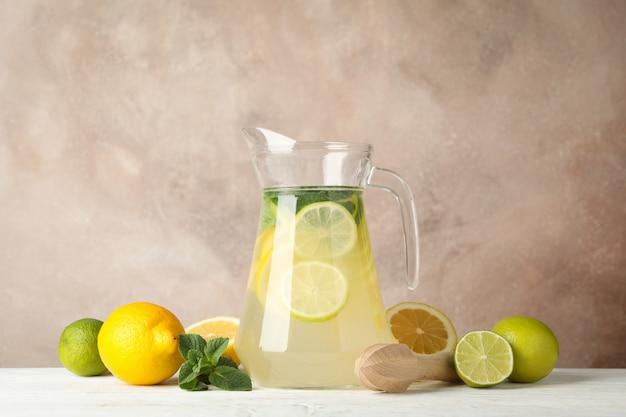 Кувшин с лимонадом и ингредиенты на деревянный стол. свежий напиток