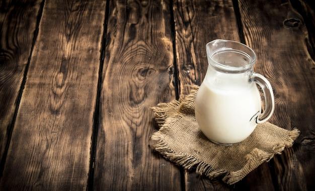 袋にミルクを入れて水差し。木製のテーブルの上。