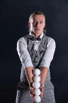 흰색 공을 가진 사업가처럼 양복을 입고 요술쟁이. 성공과 관리의 개념.