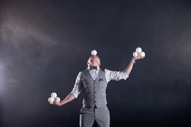 Жонглер в костюме бизнесмена с белыми шарами. концепция успеха и управления.