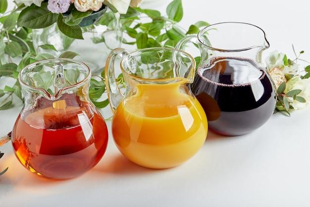 이벤트 케이터링에 다양한 주스가 담긴 주전자 사과 오렌지, 체리 및 토마토 주스