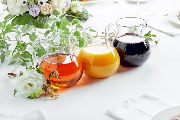 이벤트 케이터링에 다른 주스가 담긴 주전자. 사과, 오렌지, 체리, 토마토 주스.